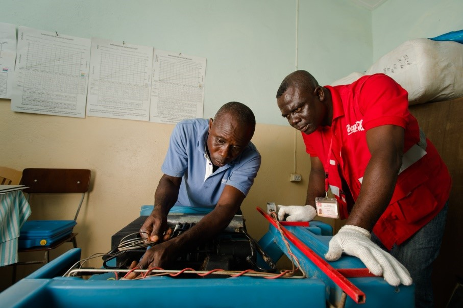 Coca-Cola Lead Cooler Technician, Maxwell Ayisi (right), and Ghana Health Service Refrigeration Technician, Livingstone Modey, repairing a dual gas/ electric vaccine refrigerator at a clinic in Peki Dzake, Ghana. Image by The Coca-Cola Company